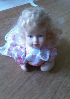 Small porcelain baby girl doll crawling