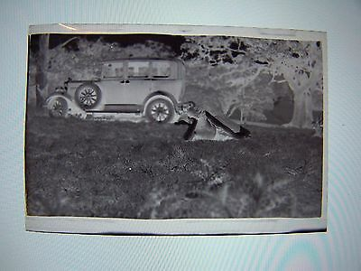 Vintage Negative Car on Roadside Wheel on Side of Car Person Laying in Grass