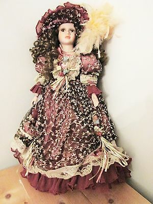A Lovely Collectable Porcelain Doll In A Burgundy Floral Dress