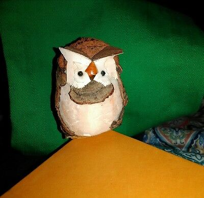 Small owl made of cork or tree bark very light cute sits on corner or uphill