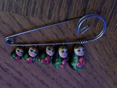 Five Russian Matryoshka dolls on a safety pin