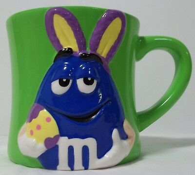 M&M Easter mug,  Blue m&m dressed as an Easter bunny rabbit on green ceramic cup