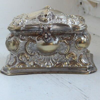 A very ornate antique silver plated casket decorated with cherub heads etc