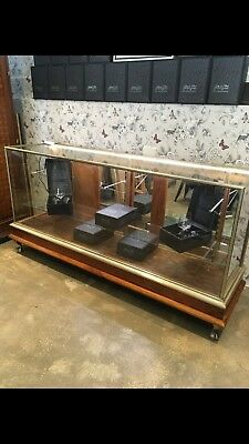 Antique nickel display cabinet with glass shelves for retail store.