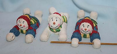 3 ceramic snowmen on bellies sledding with holes in hands to hold a pole