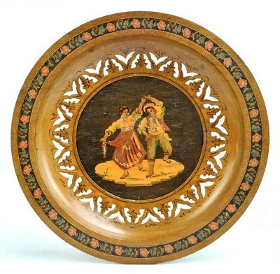 An Italian inlaid wooden plaque depicting a dancing couple within pierced border