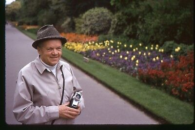 Org Kodachrome 35mm photo slide 1973 Man with a Movie camera by flowers