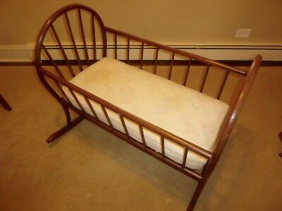 wooden baby cradle, includes mattress, brown stained finish.