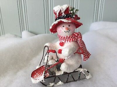 Snowman With A Bucket And Shovel On A Sled