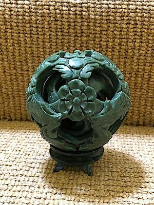 Hand carved hard green stone Chinese infinity ball with dragons and flowers.