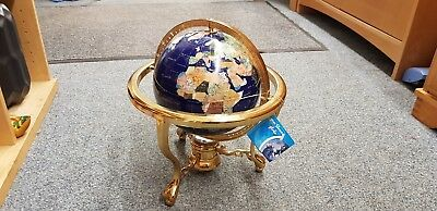 Blue semi precious gemstone globe on gold coloured stand.