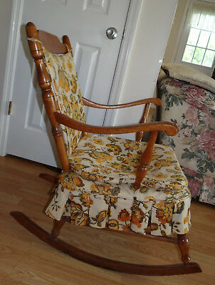 Antique wooden rocking chair, medium wood color, orange and brown cushions