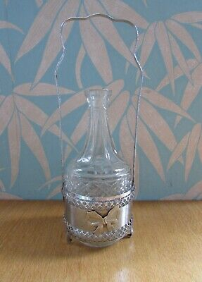 Vintage pressed glass decanter in silver plate bow tantalus, missing stopper