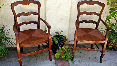 Pair Country French arm chairs, rush seats, w/ ladder backs