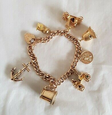An antique 9ct Yellow gold Curb link bracelet. Suspended from are eight charms.