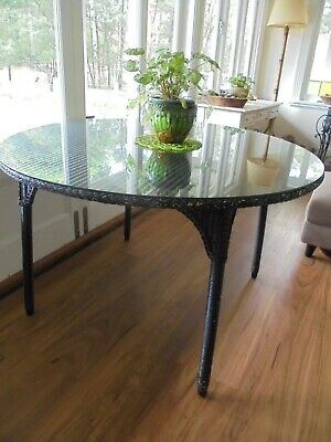 Lloyd loom dining table with glass top.