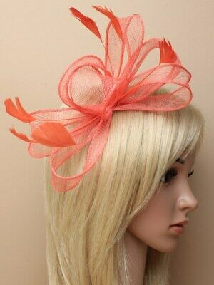 Coral fascinator with bows and feather tendrils on comb.