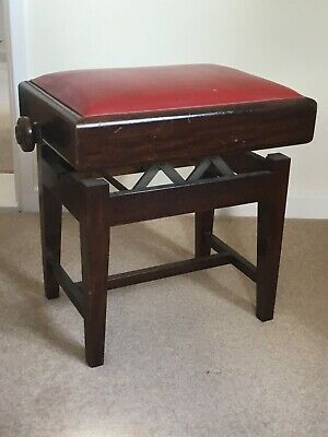 Vintage mahogany height adjustable piano stool with red cover. Condition is used