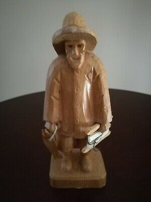 Fisherman holding 2 fishes in one hand & fishing hook in the other, carved wood.