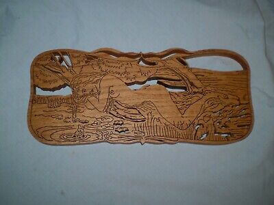 Carved wood nude woman laying next to water