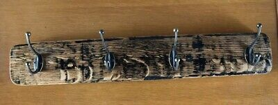 Four Coat Hooks Mounted On A Strip Of Old Whiskey Barrel