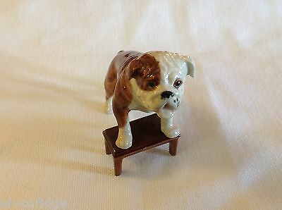 ceramic miniature dog Bulldog standing up on a bench or footstool