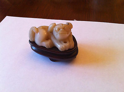 A Chinese stone figure of a reclining dog.