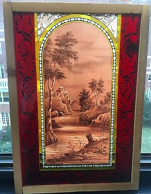 Antique painted and fired stained glass window of church overlooking a river sce