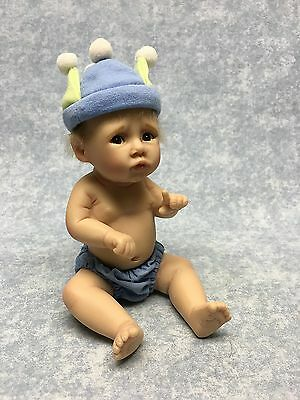 Ashton Drake Resin baby with blue & green jester hat