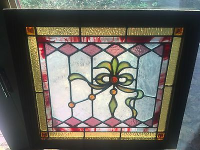 One of a pair of jeweled stained glass windows