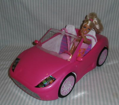 Barbie doll and pink car.
