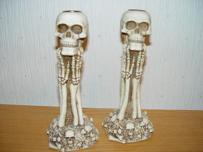 A pair of skull and skeletal candlesticks