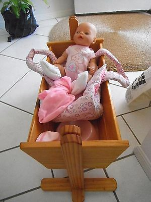 Zapf Creations Baby Born Doll with wooden cradle and plastic potty.