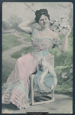 Glamour coloured postcard of seated woman in Edwardian dress.