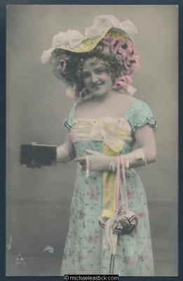 Glamour coloured postcard of woman in Edwardian dress holding a box.