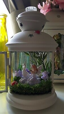 Lantern with fairy and unicorn in a miniature garden