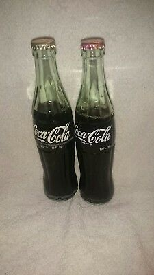 2 bottles of Coca-Cola with lids