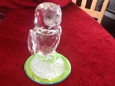 a lead crystal owl with a green tinted mirror base