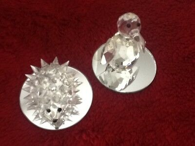 A lead crystal hedgehog and penguin with a mirrored base