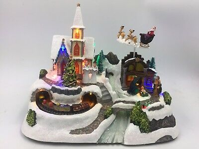 31cm Wide Animated Christmas Village with fly by Santa