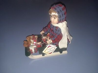 Collectors Choice Porcelain doll Christmas sleigh - Green, red, blue