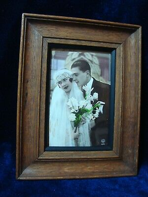 AN ANTIQUE SMALL OAK FRAME WITH 1920s 'WEDDING' POSTCARD.