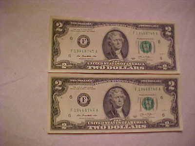 currency. two crisp uncirculated two dollar bills. sequential numbers.