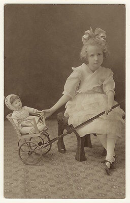 Cute Little Girl Sitting Beside Her Doll In In A Toy Stroller   (Vintage Rppc)
