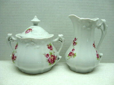 White and floral porcelain creamer and sugar.