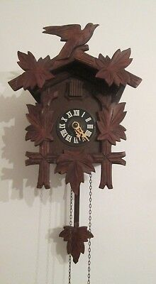 Old wooden carved with original mechanism working cuckoo clock with weights