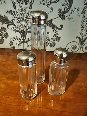 SET OF 3 SILVER PLATE AND FLUTED GLASS DRESSING TABLE BOTTLES. CIRCA 1950s