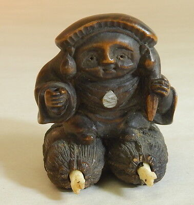 Japanese Carved Wood Netsuke of a Man with Bundle Wearing Snow Shoes