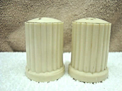 Off white plastic column shape salt & pepper shaker set.