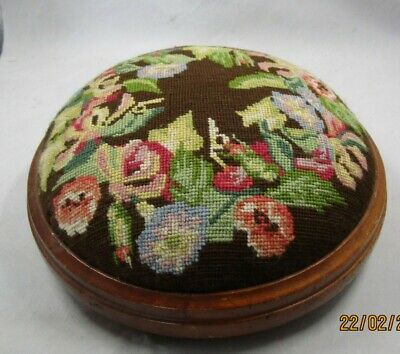 Round Antique footstool, tapestry covered on bun feet.